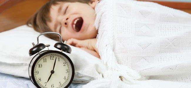 Niño bosteza con reloj
