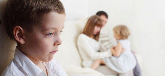 Niño triste padres y hermana de fondo