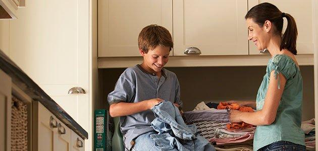Niño dobla ropa con su madre