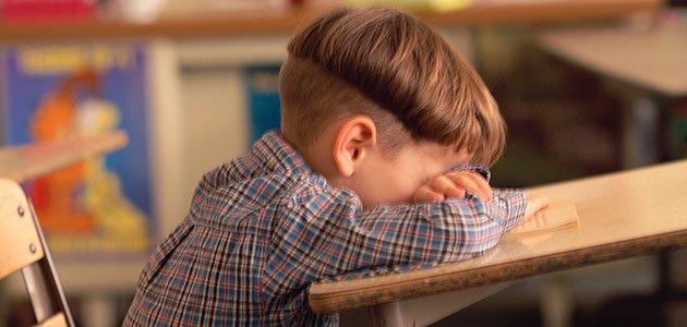 niño llora en pupitre