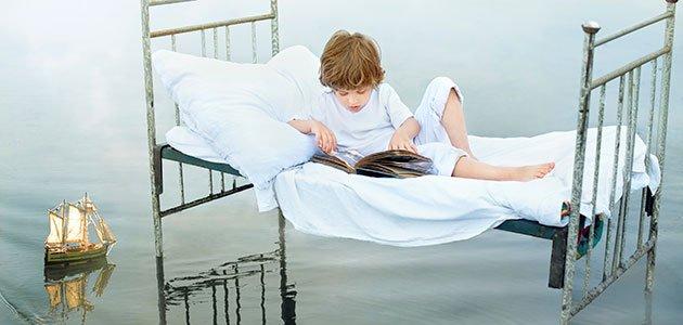 Niño lee en cama sobre el mar