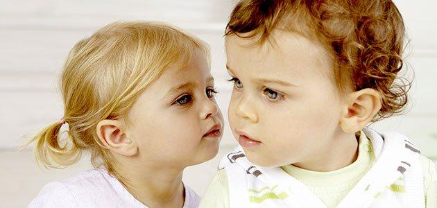 Niña da un beso a un niño