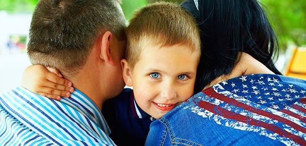 Niño abrazado por sus padres
