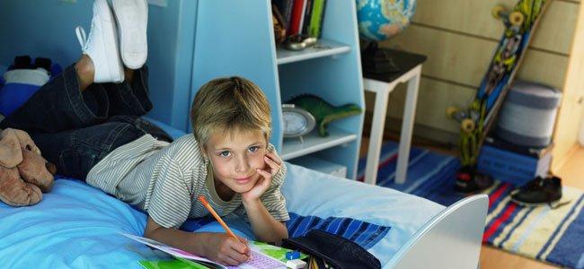 NIño hace deberes en su cuarto