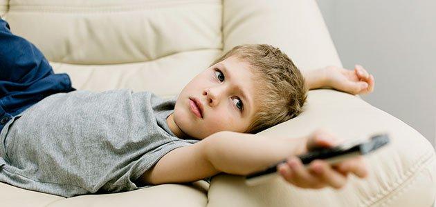 Niño tumbado ve la tele