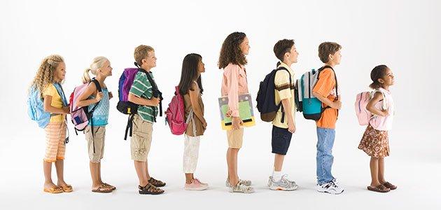 Niños con mochila en fila