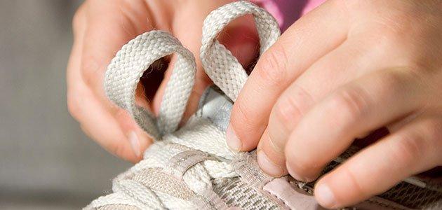 Niño atándose zapatillas de deporte