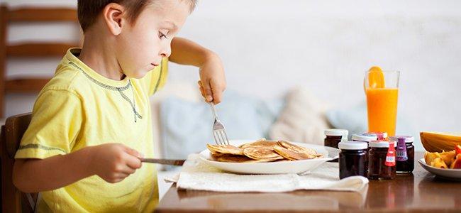 Niño en la mesa con cubiertos