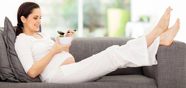 Embarazada en el sofá comiendo
