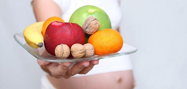 Embarazada con plato de fruta y nueces