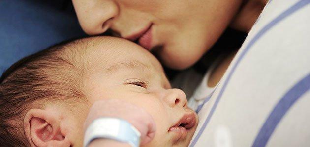 madre da un beso al bebé