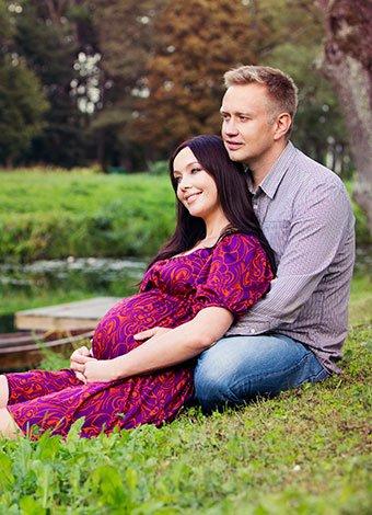 Pareja embarazada descansando junto a un rio