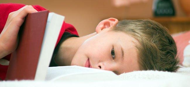 Niño lee tumbado