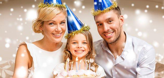 Niña con padres y tarta de cumpleaños