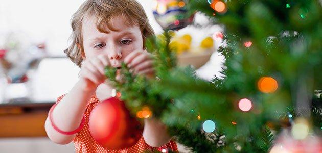 Niño coloca bola en árbol
