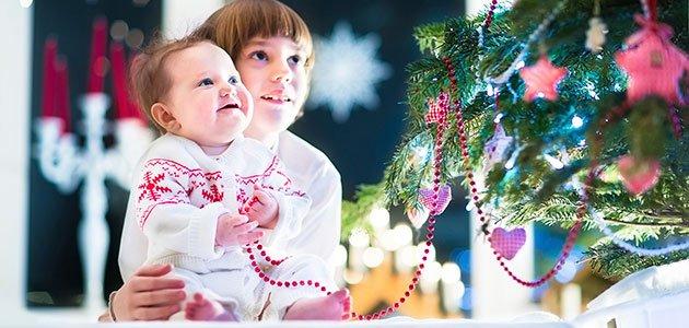 Niño y bebé junto al árbol