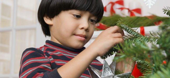 Niño decora árbol