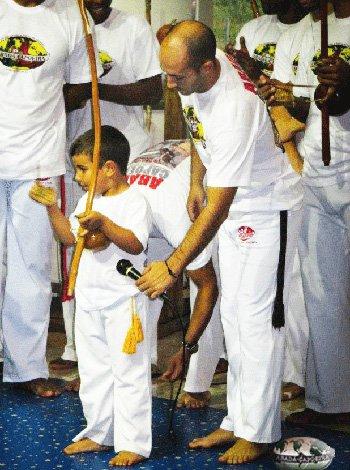 niño jugando con la capoeira y el berimbau