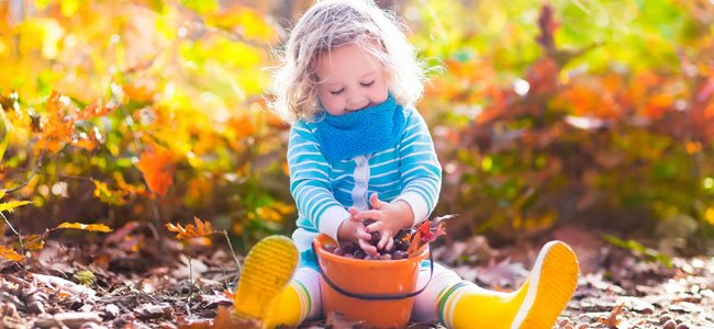 Niña juega en otoño