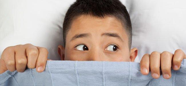 Niño asustado en cama por enuresis