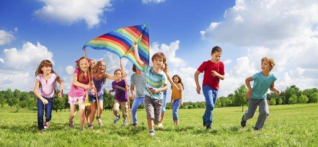 Niños juegan a correr con cometa