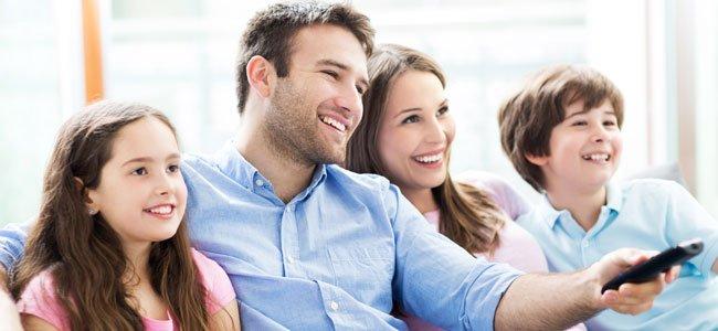 Niños ven la tele con los padres