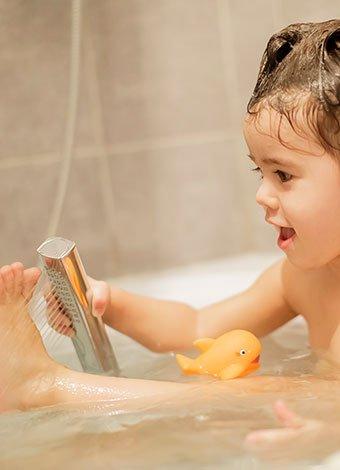Niña en la bañera con la ducha