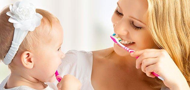 Madre se cepilla dientes con bebé