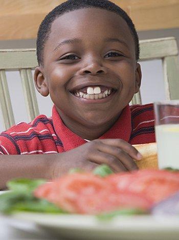 Niño sonriendo en la mesa con comida