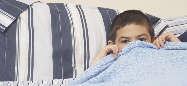 Niño se tapa en la cama con sábana