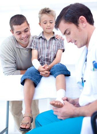 Médico vendando tobillo de niño