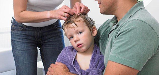 padres revisan la cabeza a un niños
