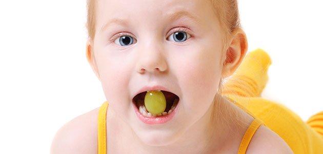 Niña con uva en la boca