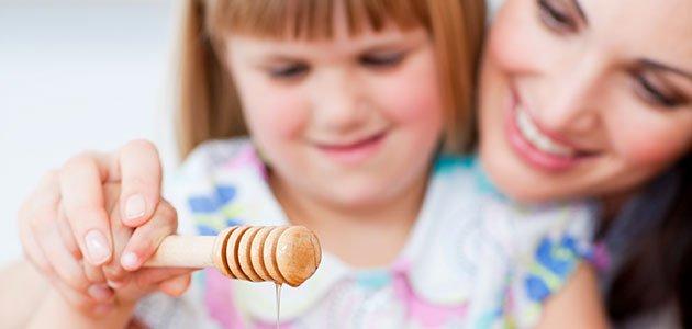 Niña con su madre echando miel en tortitas