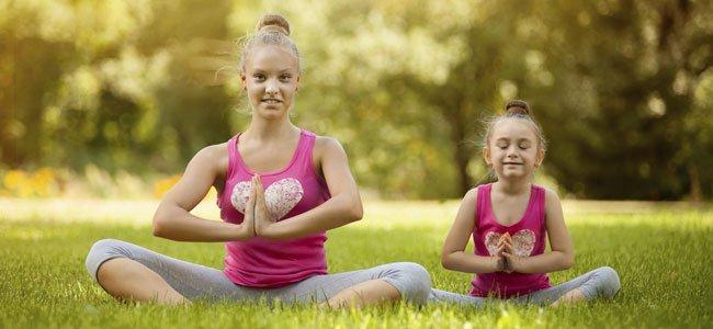 Niña hace yoga con su hermana