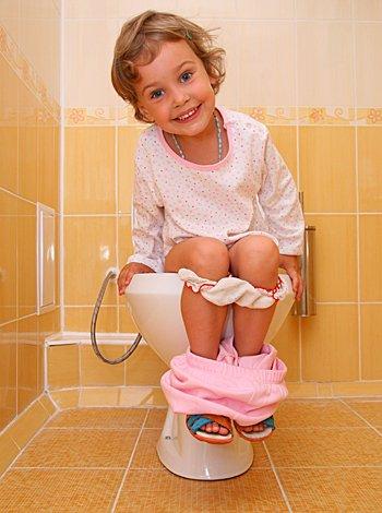 niña sentada en el inodoro
