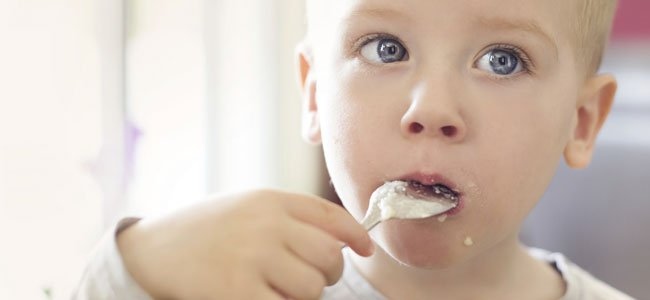 Niño come con cuchara