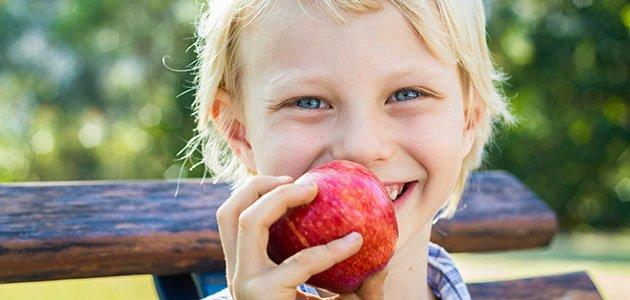 Niño come manzana