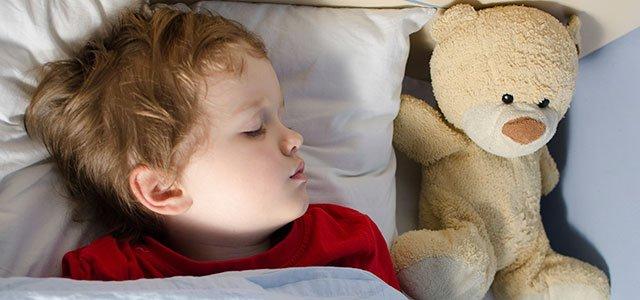 Niño duerme con osito