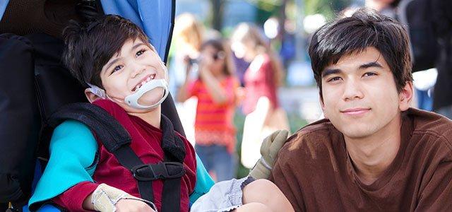 Padre con hijo en silla de ruedas