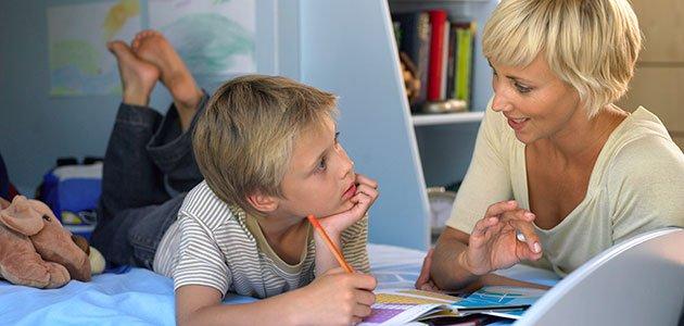 Niño hace deberes con su madre