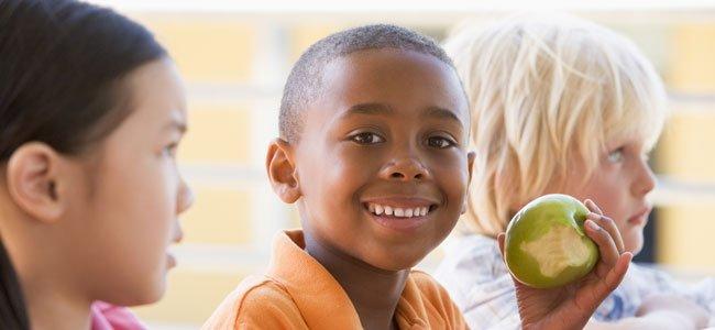 Niño negro come manzana