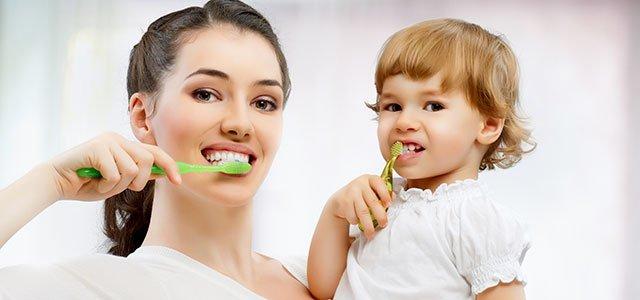 Madre con hijo cepillándose los dientes