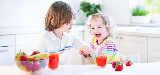 Niños toman zumo de fresas