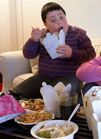 Niño comiendo comida rápida