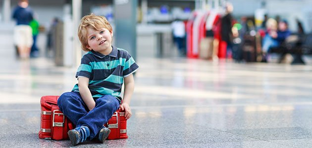 Niño sentado en maleta en aeropuerto